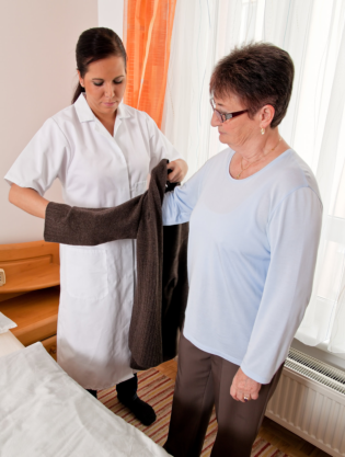 caregiver assisting elder in dressing